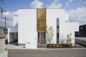 漆喰の壁に木の格子がアクセントになった、キューブ型のモダンな家